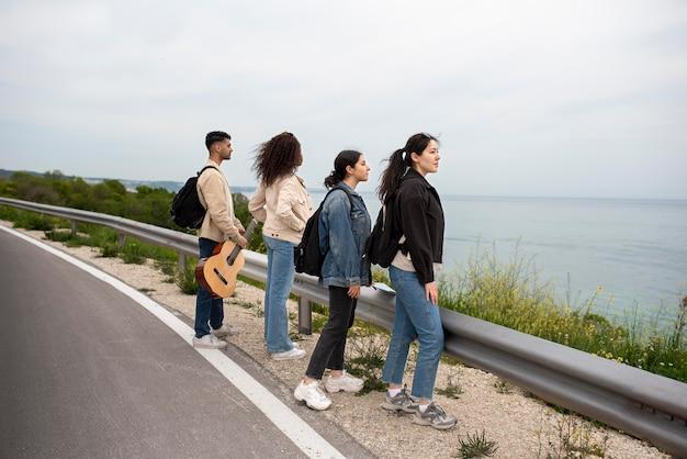 Amigos em filmagem completa olhando para o mar
