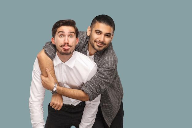 Amigos em pé desfrutando de abraços e olhando para a câmera com um sorriso, uma cara engraçada e a língua de fora