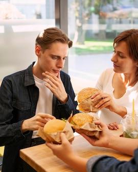 Amigos em restaurante de fast food comendo