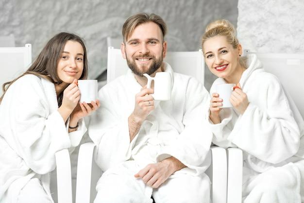 Amigos em roupão de banho relaxando com xícaras de chá, sentados na sala de sal. aplicação de terapia de sal no spa