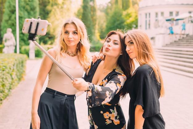 Amigos em roupas elegantes, fazendo selfie no telefone inteligente.