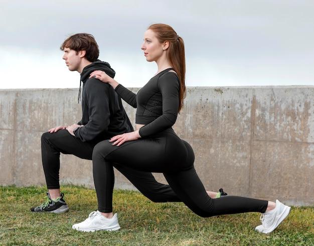 Amigos em roupas esportivas se exercitando ao ar livre Foto gratuita