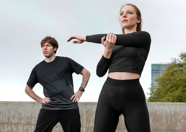 Amigos em roupas esportivas se exercitando ao ar livre