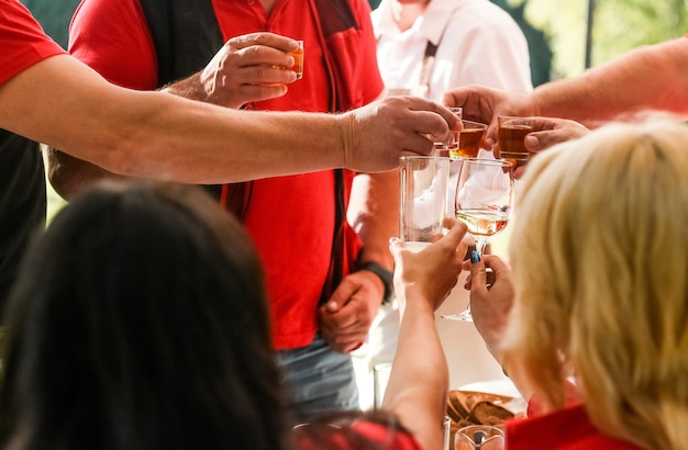 Amigos em roupas vermelhas levantou seus óculos juntos no feriado