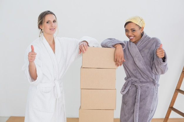 Amigos em roupões de banho com caixas gesticulando polegares para cima em casa nova