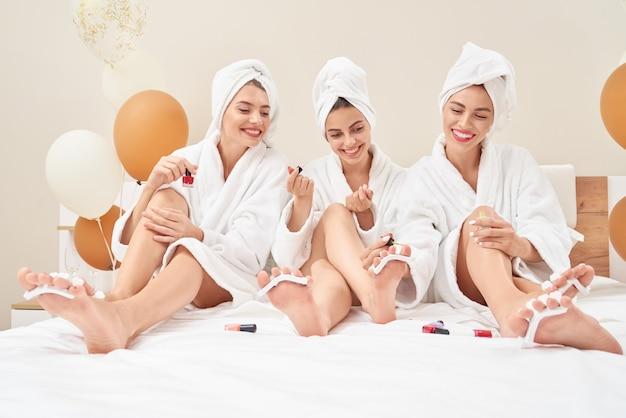 Amigos em toalhas e roupões fazendo pedicure.