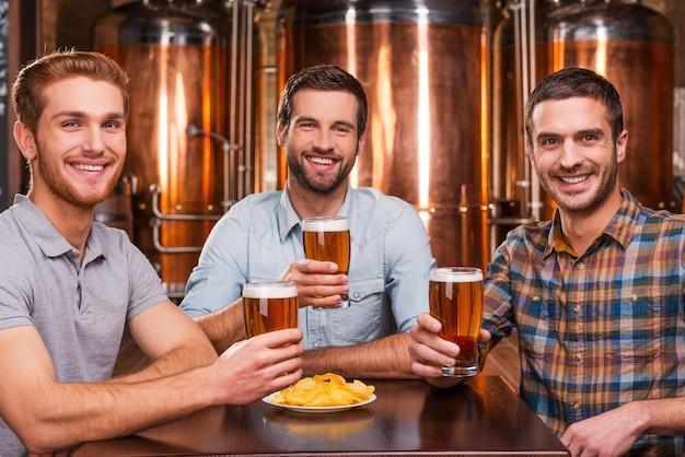 Amigos em um bar de cerveja. três jovens alegres em roupas casuais segurando copos com cerveja e sorrindo enquanto estão sentados em um bar de cerveja e em frente a recipientes de metal