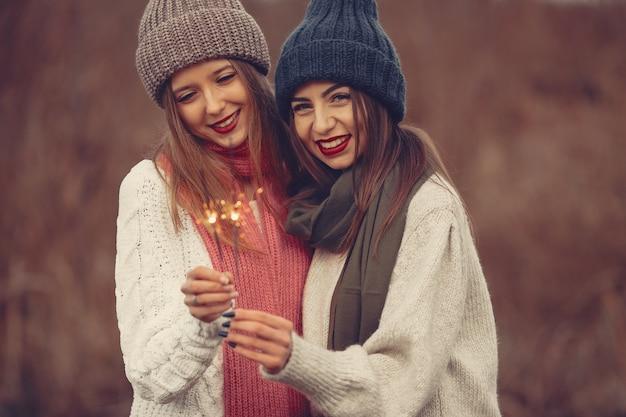 Amigos em um parque de inverno. meninas com chapéus de malha. mulheres com estrelinhas.
