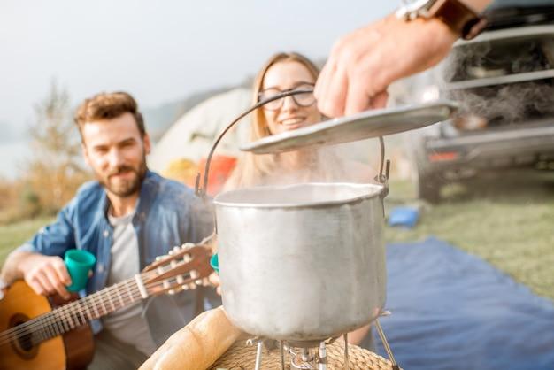 Amigos em um saboroso jantar com sopa cozida no caldeirão durante o piquenique no acampamento