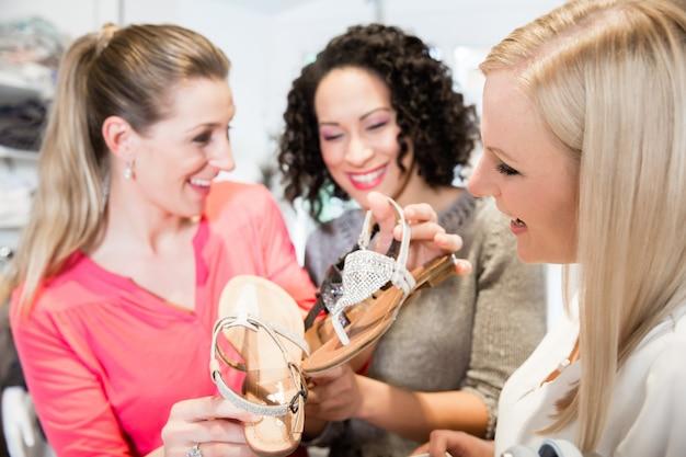 Amigos em uma viagem de compras discutindo sandálias e sapatos de compra
