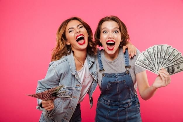 Amigos emocionais de duas mulheres bonitas segurando dinheiro