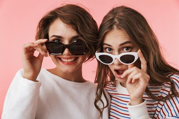 Amigos emocionais de mulheres jovens isolados sobre o fundo da parede rosa usando óculos escuros.