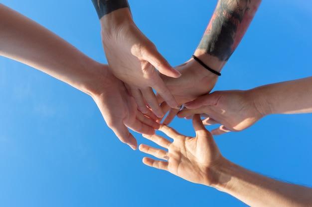 Amigos, empilhando as mãos