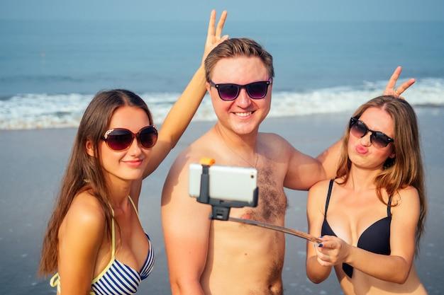 Amigos engraçados fazem uma foto em um autoadesivo na praia