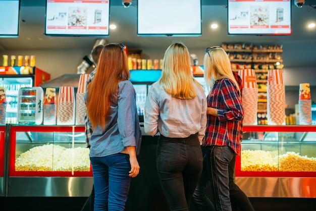 Amigos escolhendo comida no bar do cinema