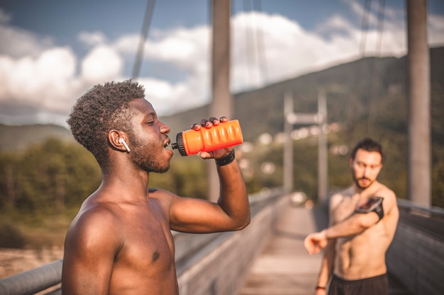Amigos esportivos treinando ao ar livre e descansando depois de uma corrida