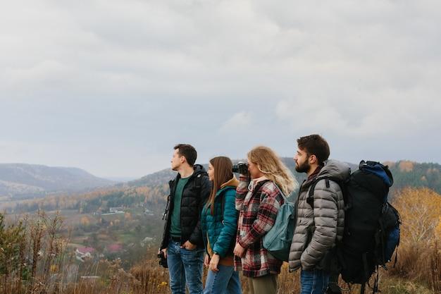 Amigos estão aproveitando o clima ensolarado de outono enquanto caminham nas montanhas