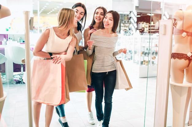 Amigos estão conversando entre si e entrando em uma loja de lingerie