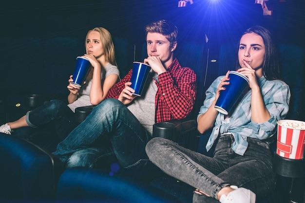 Amigos estão sentados juntos e bebendo coca-cola ao mesmo tempo