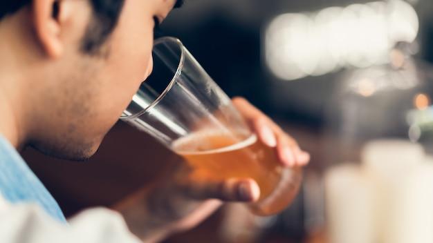 Amigos estão sorrindo, felizes festejando no bar e falando e tilintando garrafas com bebidas.