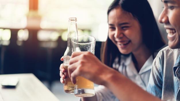 Amigos estão sorrindo, felizes festejando no bar e falando e tilintando garrafas com bever