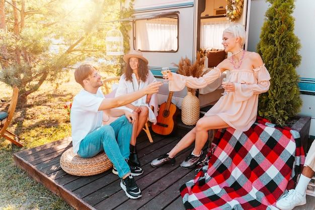 Amigos fazem piquenique com um trailer em um prado verde
