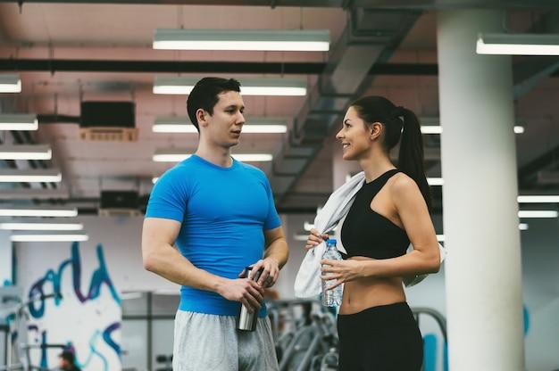 Amigos fazem uma pausa no exercício físico no ginásio