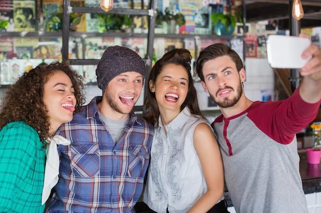 Amigos fazendo caretas enquanto falam selfie em restaurante