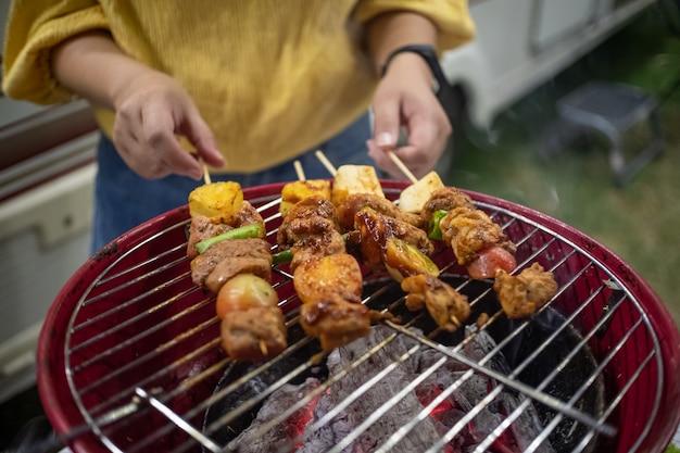 Amigos fazendo churrasco de churrasco grelhados em fogo quente na natureza. festa do jantar à noite