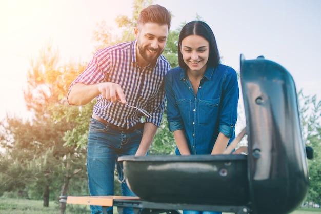 Amigos fazendo churrasco e almoçando na natureza. casal se divertindo enquanto come e bebe em um pic-nic - pessoas felizes na festa de churrasco.