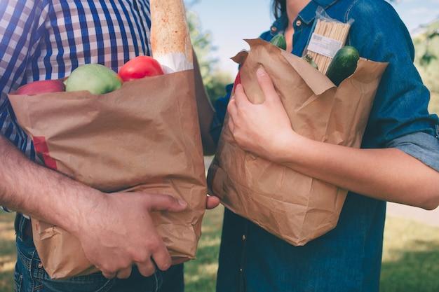 Amigos fazendo churrasco e almoçando na natureza. casal se divertindo enquanto come e bebe em um piquenique - pessoas felizes na festa de churrasco.