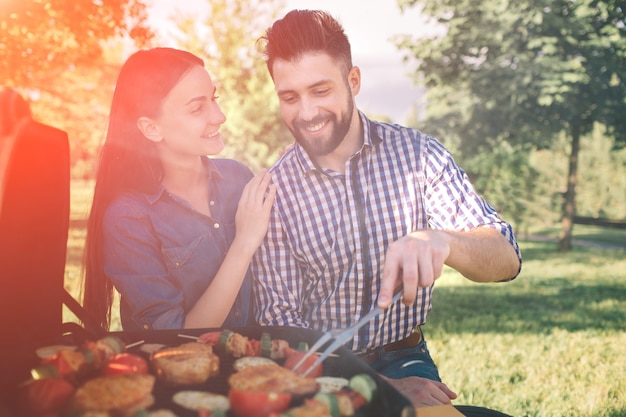 Amigos fazendo churrasco e almoçando na natureza