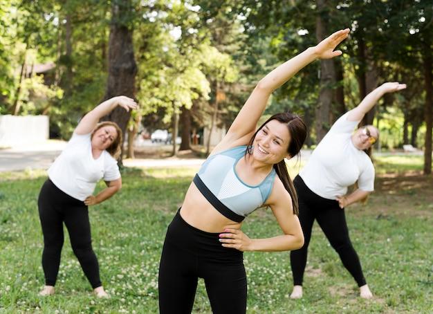 Amigos fazendo exercícios de alongamento no parque