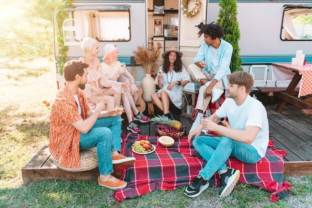 Amigos fazendo piquenique com um trailer em um dia ensolarado