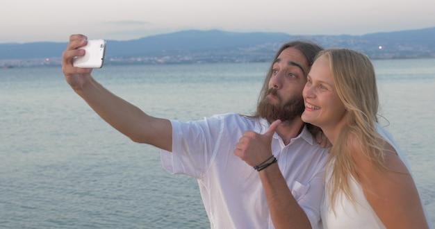 Amigos fazendo selfie feliz e positiva na praia