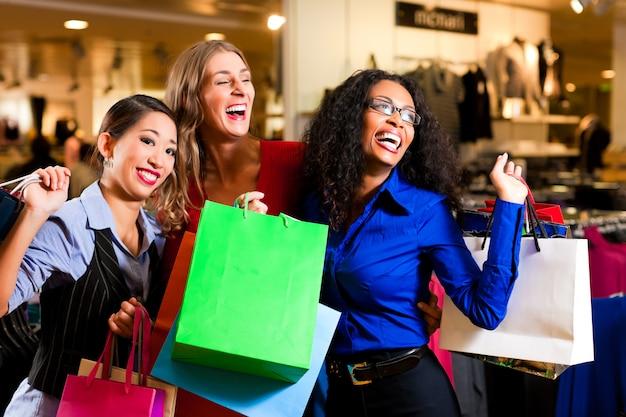 Amigos, fazer compras com sacolas no shopping