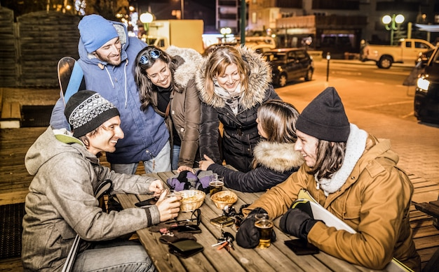 Amigos felizes bebendo cerveja e comendo batatinhas no bar depois do esqui