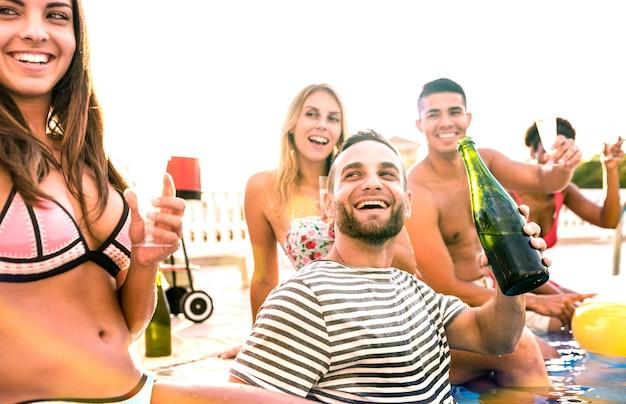 Amigos felizes bebendo champanhe de vinho branco na festa na piscina