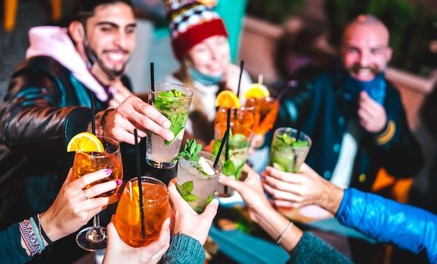 Amigos felizes brindando bebidas em bar noturno com máscara aberta