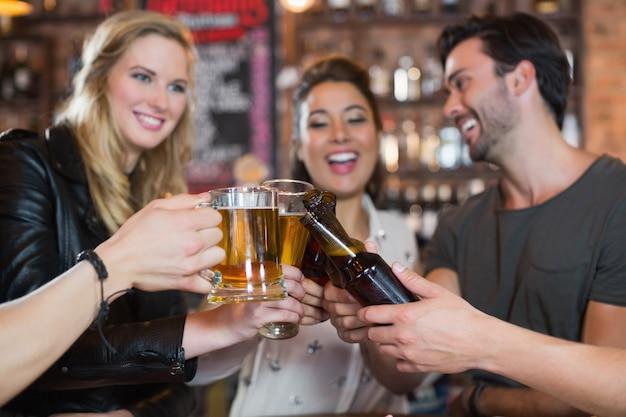 Amigos felizes brindando canecas e garrafas de cerveja