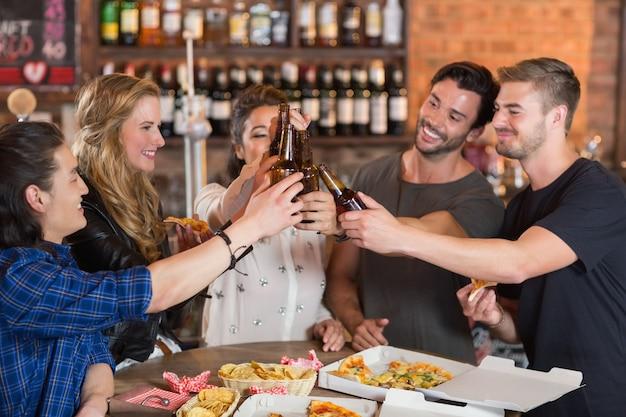 Amigos felizes brindando garrafas de cerveja com pizzas na mesa
