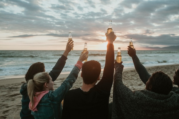 Amigos felizes brindando na praia