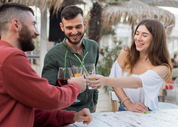 Amigos felizes brindando uma dose média