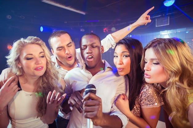 Amigos felizes cantando no karaokê