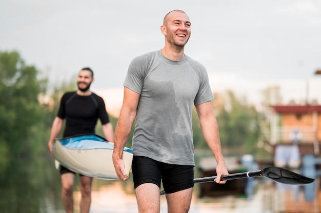 Amigos felizes, carregando uma canoa