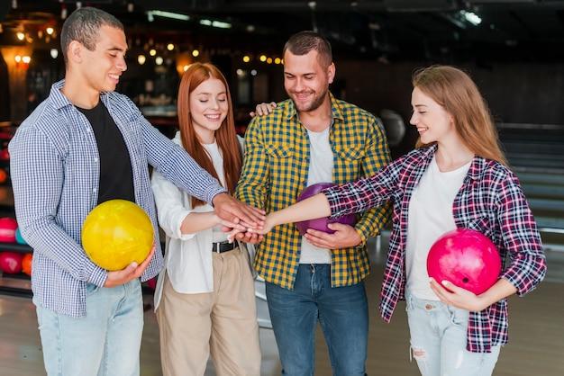 Amigos felizes com bolas de boliche coloridas em um clube de boliche