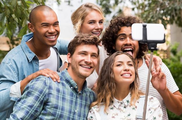Amigos felizes com cara engraçada tirando uma foto com um bastão de selfie