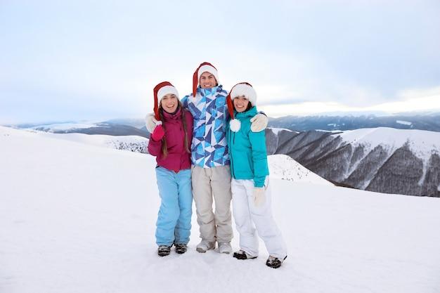 Amigos felizes com chapéus de papai noel no pico nevado de uma montanha no resort