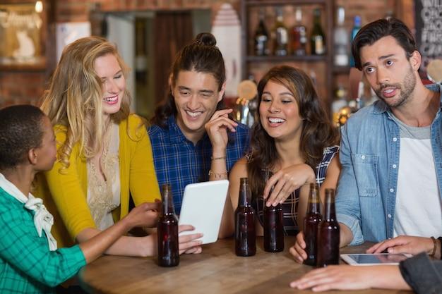 Amigos felizes com garrafas de cerveja usando tablet digital