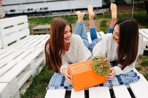 Amigos felizes com um presente de laranja